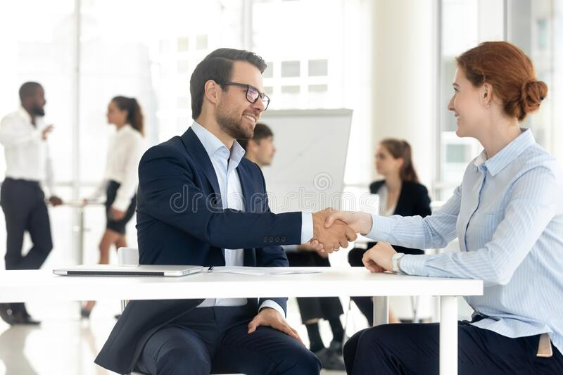 Smiling diverse business partners handshake closing deal at meeting royalty free stock images