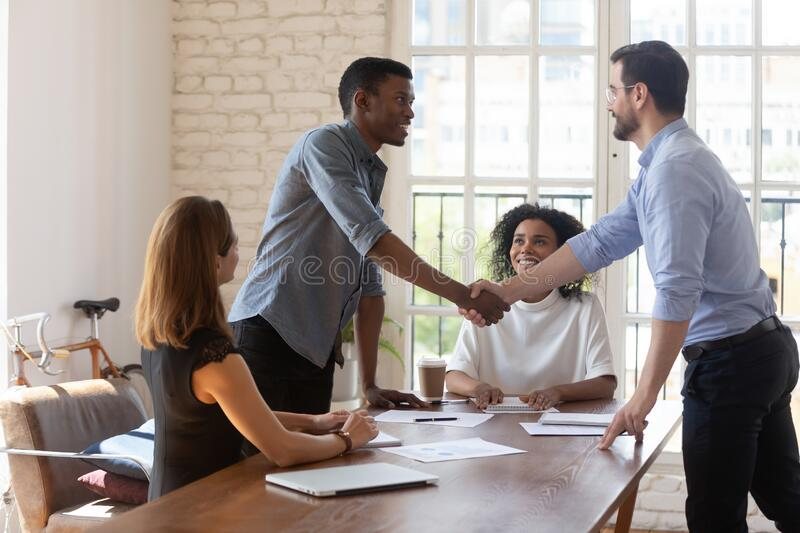 Smiling diverse business partners shaking hands after signing contract royalty free stock photo
