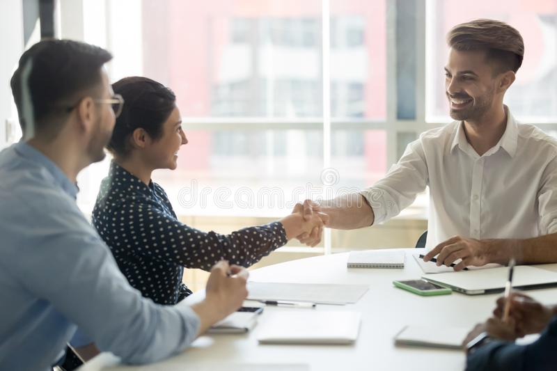 Smiling diverse partners handshake collaborating at office meeting royalty free stock image