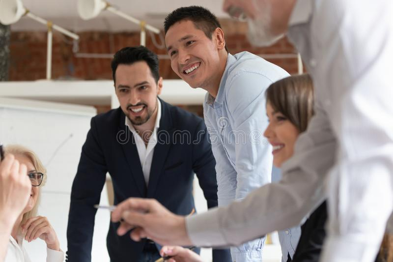 Smiling diverse colleagues brainstorm at office meeting. Smiling multiracial colleagues speak collaborating at business meeting gathering in office, happy royalty free stock photography