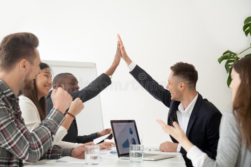 Smiling colleagues giving high five excited by business results stock photo