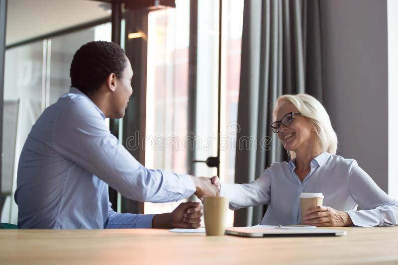 Smiling diverse colleagues handshake greeting at meeting. Smiling middle-aged Caucasian businesswoman handshake african American business partner or client get royalty free stock photo