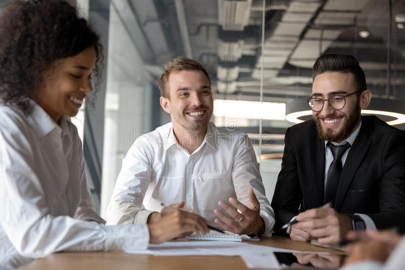 Smiling diverse colleagues having fun at business briefing in office royalty free stock photography