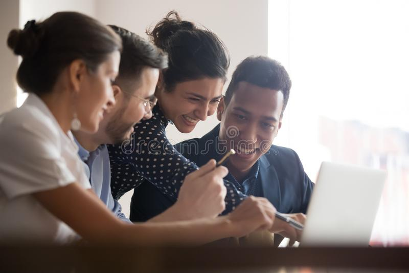 Smiling diverse colleagues laugh brainstorming using laptop stock photo