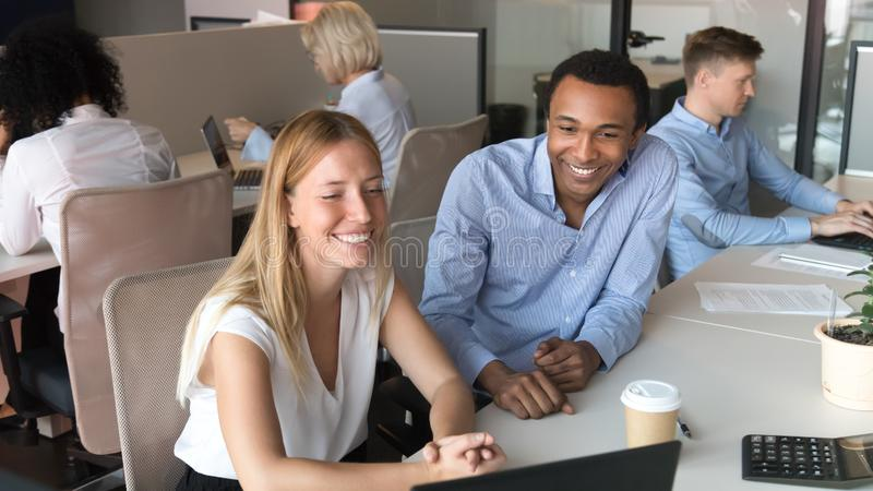Smiling diverse colleagues laugh watching video on laptop in office stock photo