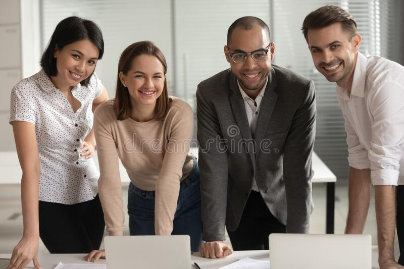 Smiling diverse colleagues posing for picture at workplace stock photography