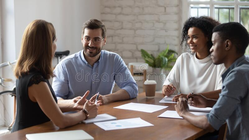 Smiling diverse colleagues discussing project strategy at briefing royalty free stock images