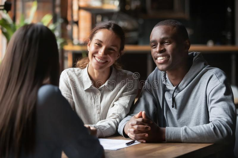 Smiling diverse couple listening to financial advisor or realtor stock photo