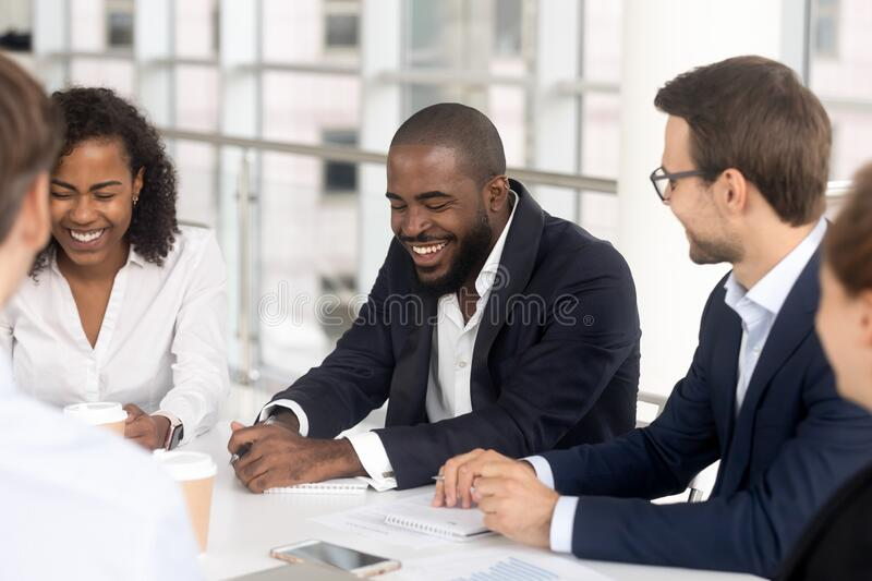 Smiling diverse employees laugh brainstorming at office meeting stock photos