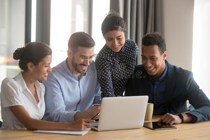 Smiling diverse employees laugh cooperating at laptop in office stock photography