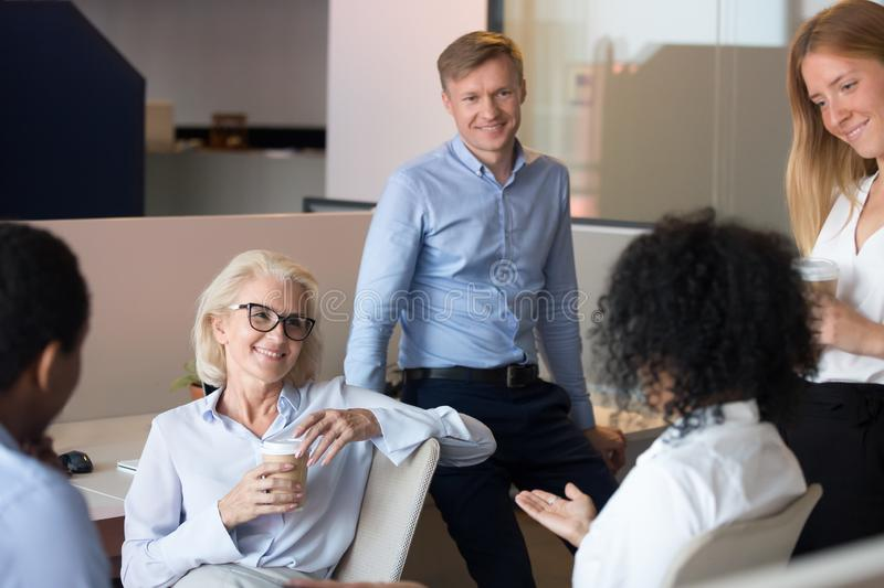 Smiling diverse employees brainstorm sharing ideas at workplace. Smiling diverse employees listen to female colleagues talking sharing ideas at informal team royalty free stock photography