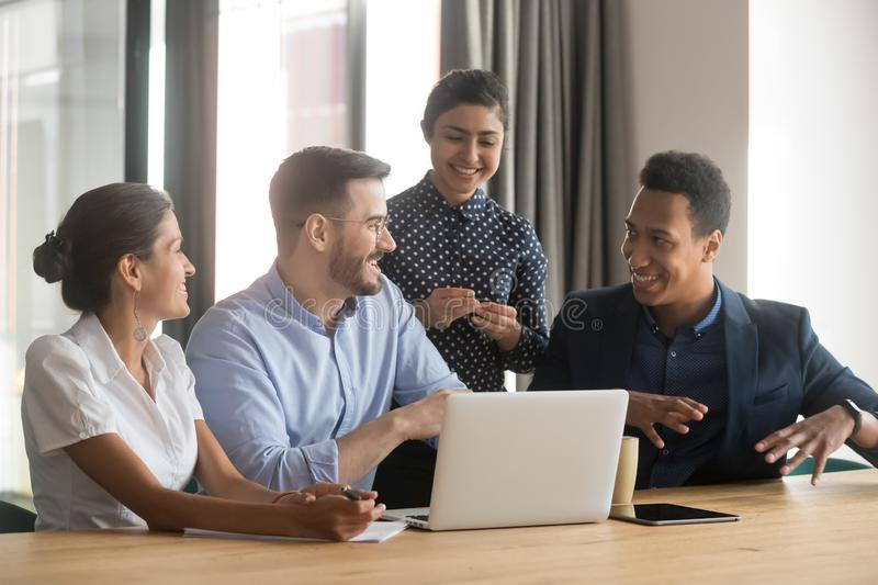 Smiling diverse employees talk brainstorming in office using laptop stock image