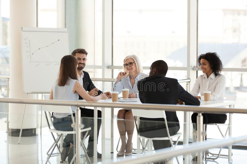 Smiling diverse employees talking at meeting table in conference stock image
