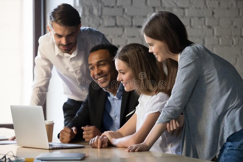 Smiling diverse employees team watching webinar on laptop together royalty free stock photos