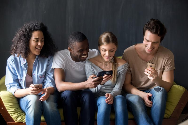 Smiling diverse friends discussing new apps for mobile phone. royalty free stock photos