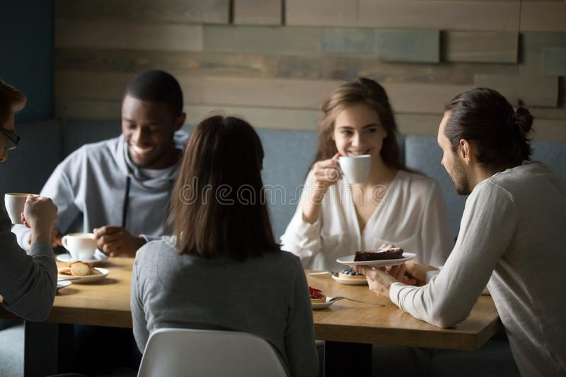 Smiling diverse friends enjoying coffee and desserts in cafe royalty free stock images