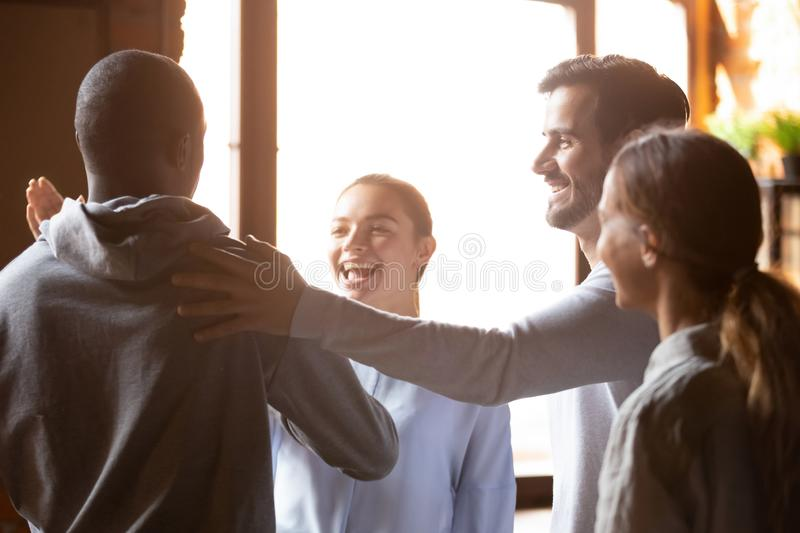 Smiling diverse friends greeting in cafe, welcoming at meeting royalty free stock photography