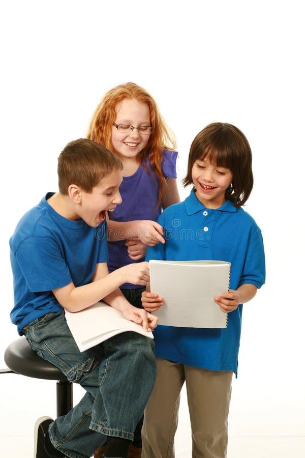 Smiling diverse kids reading. Diverse kids reading scripts and having fun royalty free stock photos