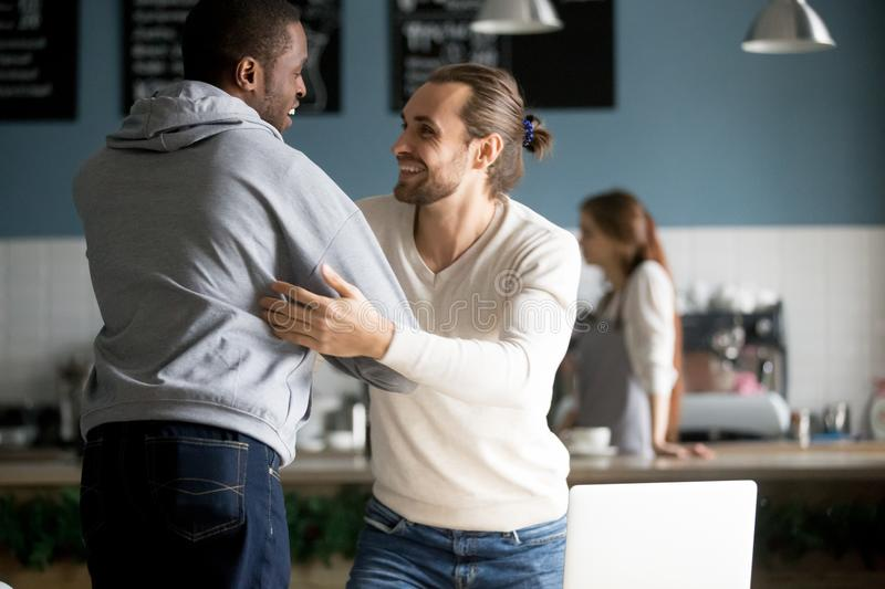 Smiling diverse male friends embracing greeting at meeting in ca. Smiling diverse male buddies embracing greeting in cafe, happy millennial men best friends royalty free stock image