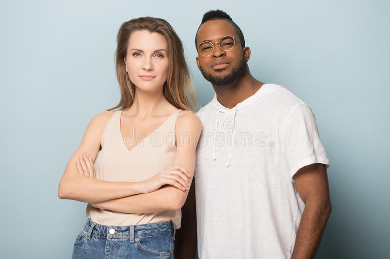 Smiling diverse man and woman posing for picture in studio. Portrait of happy african American men and Caucasian women stand isolated on blue studio background royalty free stock photography