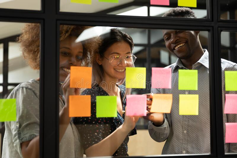 Smiling multiracial colleagues develop project on sticky notes royalty free stock photography