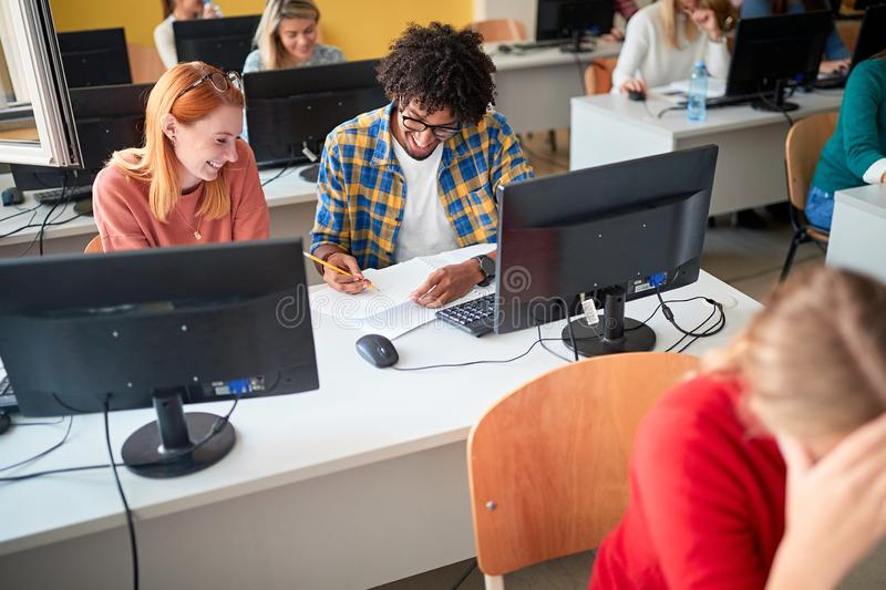 Smiling diverse students in an exam in a classroom stock image
