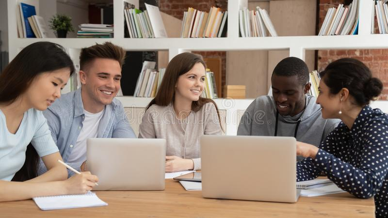 Smiling diverse students talk studying in library together royalty free stock photo
