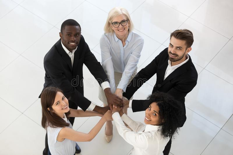 Smiling diverse team employees stack pile of hands top view royalty free stock images