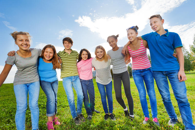 Smiling diversity friends standing on grass in row royalty free stock photography