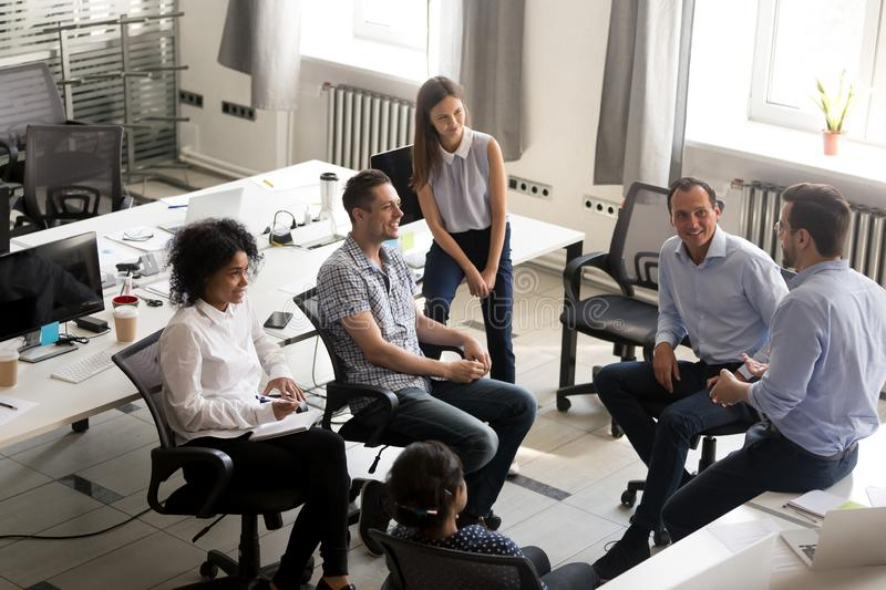 Smiling diversity team of employees listening to business coach. Smiling diversity team of employees, interns sitting circle, listening to business coach on stock image