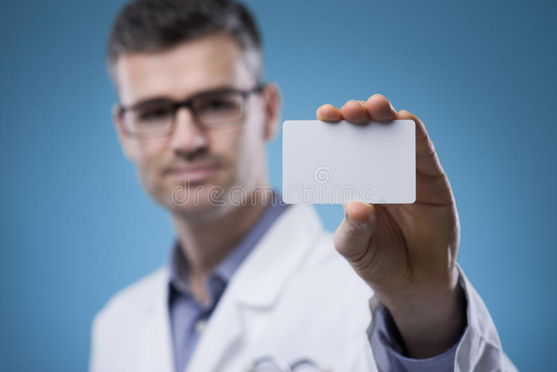 Smiling doctor with business card stock images