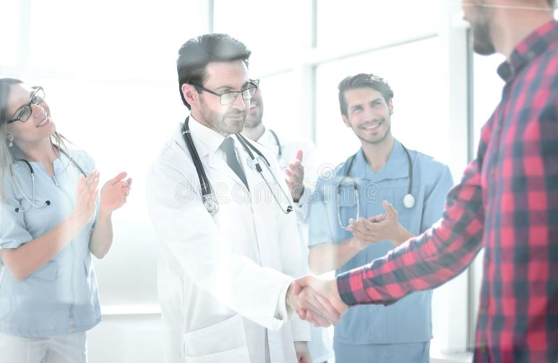 Thankful patient shaking doctors hand royalty free stock photo