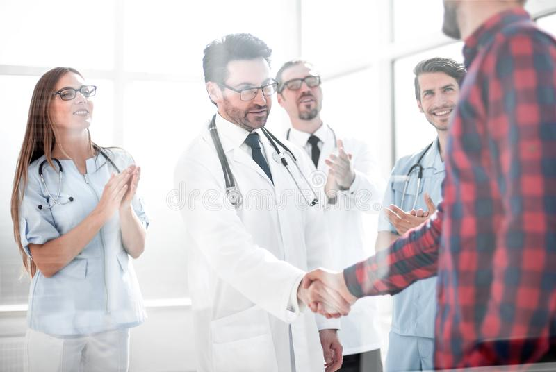 Thankful patient shaking doctors hand stock photography