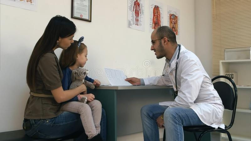 Smiling doctor explaining cardiogram to mother and little girl stock photo