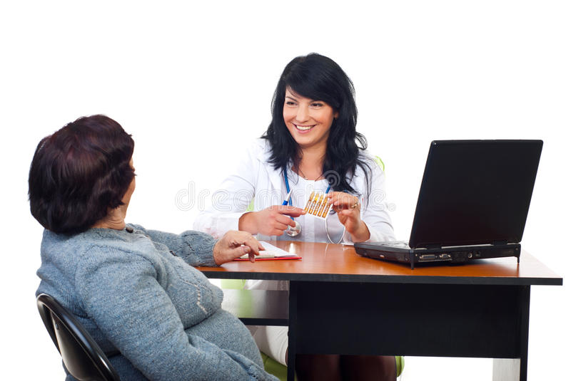 Smiling doctor giving treatment to elderly woman. Smiling doctor giving treatment ampules or showing and explain about flu vaccine to elderly woman in office stock photos