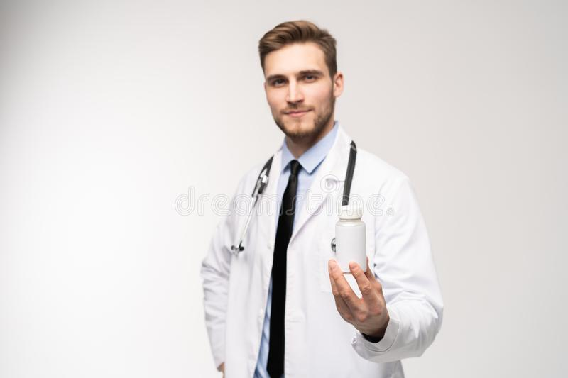 Smiling doctor holding a bottle of tablets or pills with a blank white label for treatment of an illness or injury. Smiling doctor holding a bottle of tablets royalty free stock image