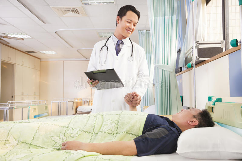 Smiling doctor holding patient hand to encourage him stock images