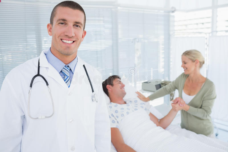 Smiling doctor looking at camera with his patient behind royalty free stock images
