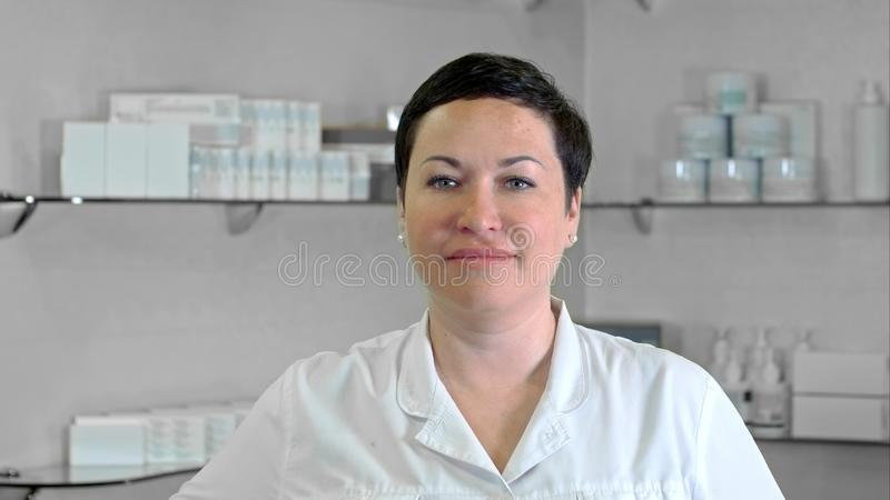 Smiling doctor looking at camera in medical office royalty free stock images