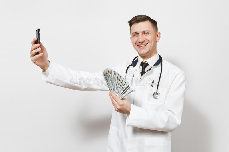 Smiling doctor man isolated on white background. Male doctor in medical uniform doing selfie on mobile phone, holding. Bundle of dollars, banknotes, cash money royalty free stock photo