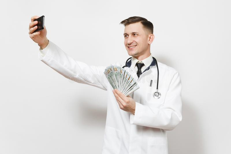 Smiling doctor man isolated on white background. Male doctor in medical uniform doing selfie on mobile phone, holding royalty free stock images
