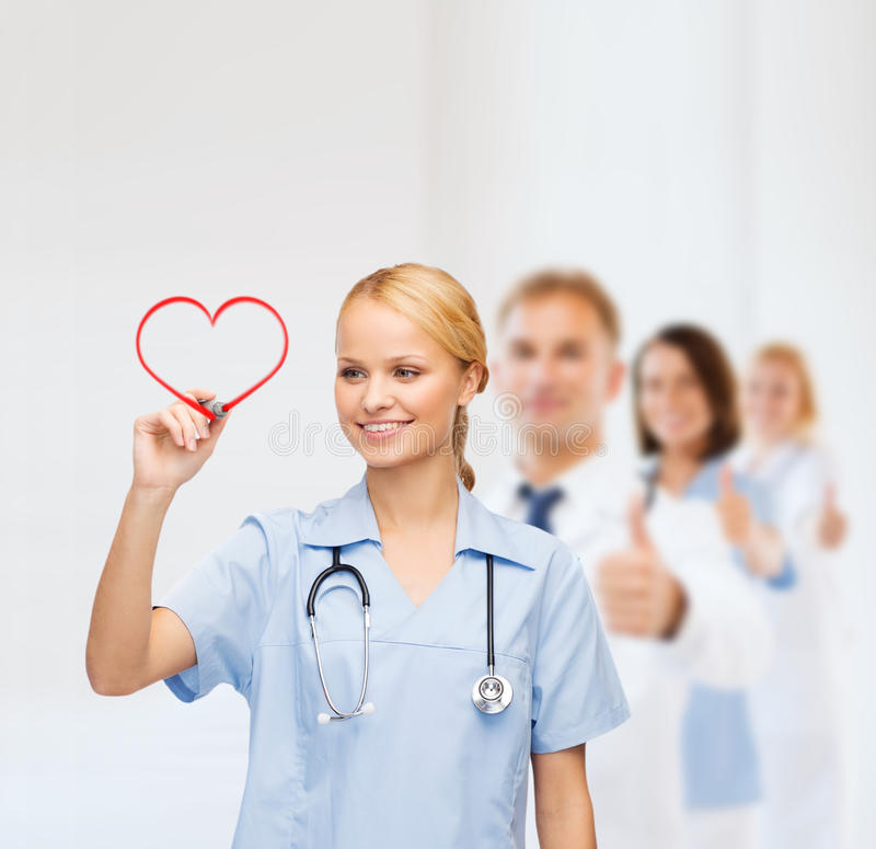 Smiling doctor or nurse drawing red heart stock images