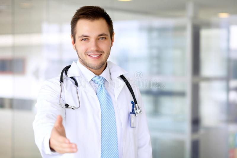 Smiling doctor is offering helping hand stock photo