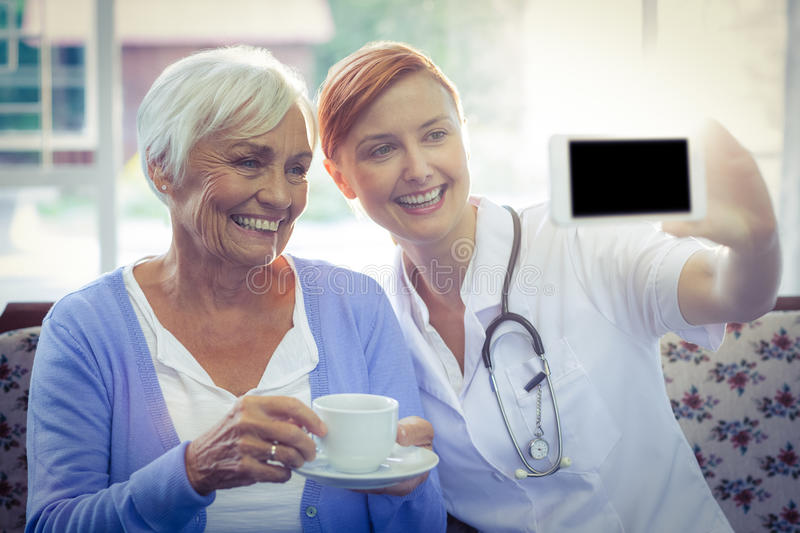 Smiling doctor and patient looking at phone while having tea. At home stock photo
