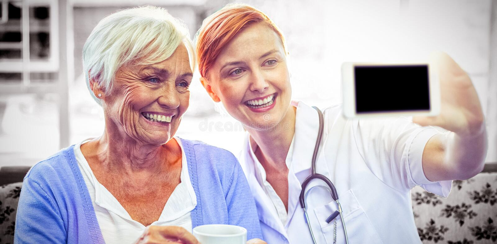 Smiling doctor and patient looking at phone while having tea. At home royalty free stock photo