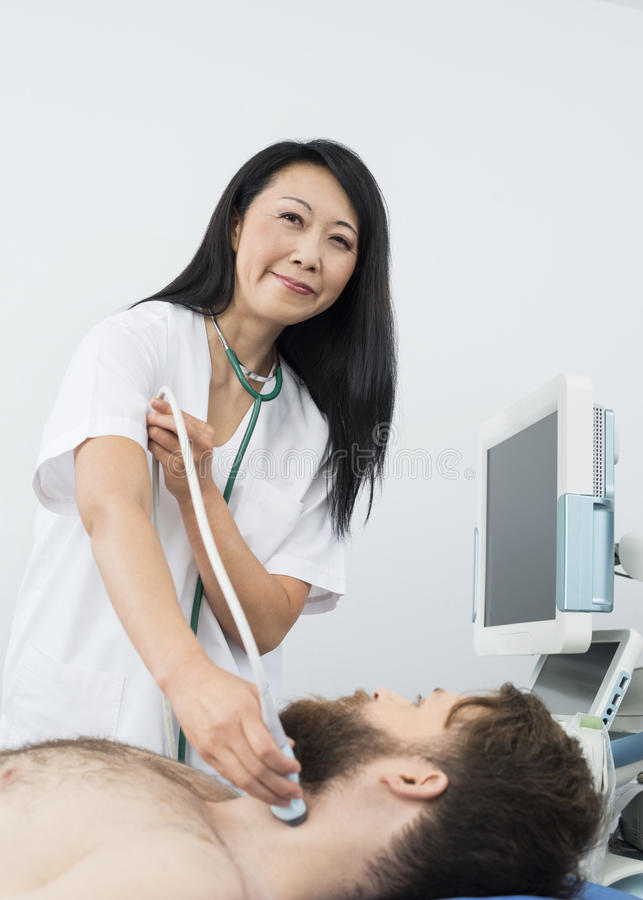 Smiling Doctor Performing Thyroid Ultrasound Test On Patient. Portrait of smiling female doctor performing thyroid ultrasound test on male patient in hospital royalty free stock photo