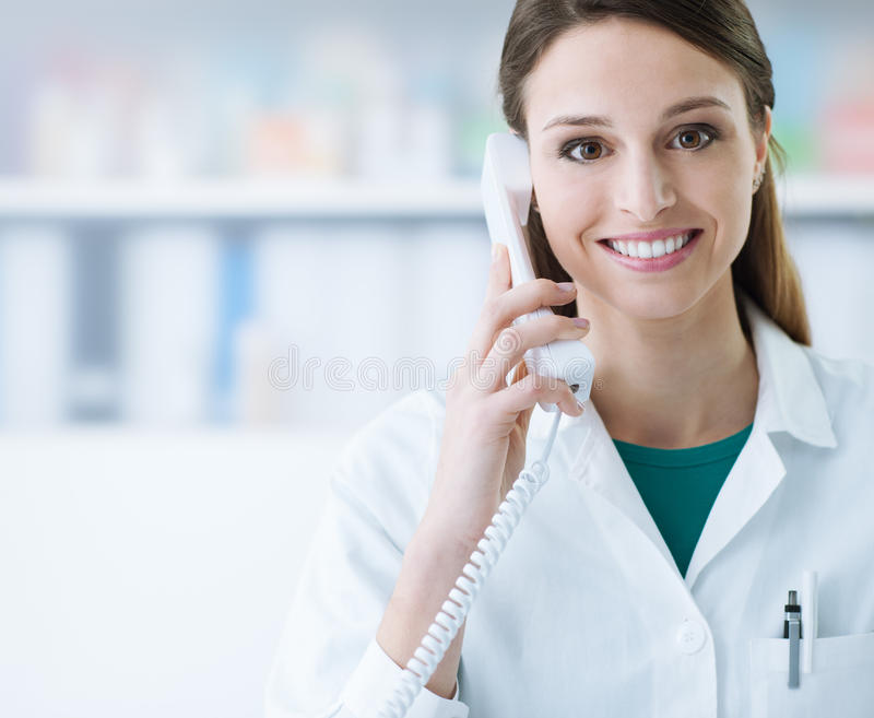 Smiling doctor phone calling. Smiling female doctor holding a receiver and answering phone calls, medical service stock photos