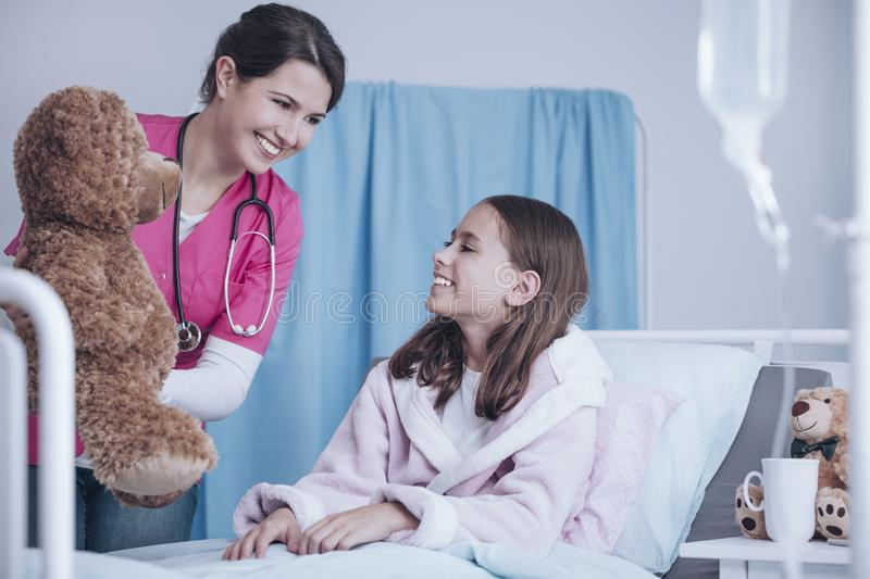 Smiling doctor in pink uniform giving plush toy to happy sick ch royalty free stock photo