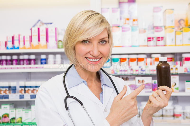 Smiling doctor pointing a drug bottle. In the pharmacy royalty free stock images