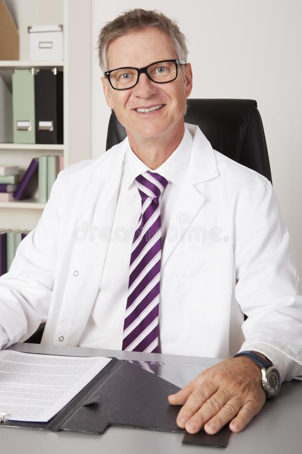 Smiling doctor sitting working at his desk stock images